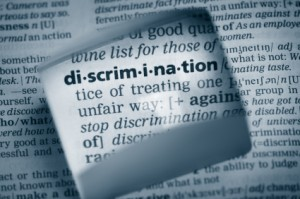 "Photo of the word ""discrimination"" in type text, with the definition of the word in the background."